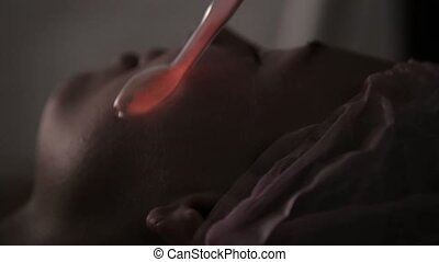 beautician does electric darsonval massage procedure for female client in a dark