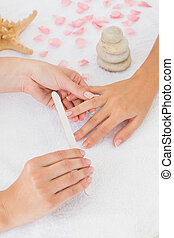 Beautician filing female client's nails at spa beauty salon