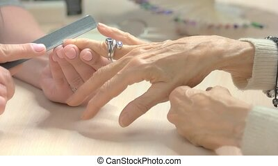 Beautician filing nails to elderly client.