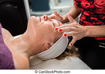 Beautician Giving Face Massage To Female Customer