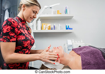 Beautician Giving Face Massage To Woman In Beauty Parlor -...