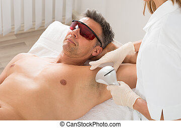 Beautician Giving Hair Removal Treatment To Mature Man In Beauty Saloon