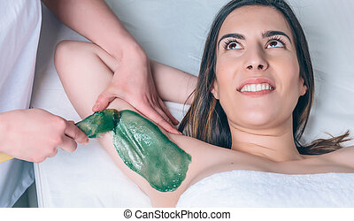 Beautician hands doing depilation in woman armpit with wax...