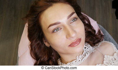 Beautician in black gloves makes permanent makeup correction of the shape of the eyebrows to a young beautiful girl. Microblading, eyebrow tattoo in a beauty salon.