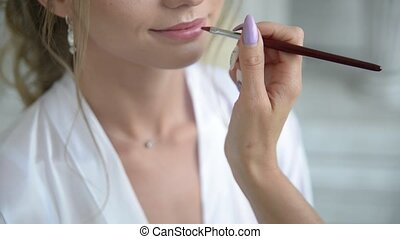 beautician in the beauty salon paints lips with a pencil to a young girl. the process of preparing for the procedure make-up