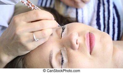 Beautician increases eyelashes for beautiful girl. Eyelash...