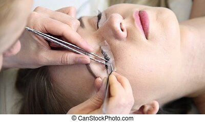 Beautician increases eyelashes for beautiful girl. Eyelash...