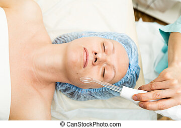 Beautician makes darsonvalization to young woman. The cosmetic procedures for the face. Beauty treatments in the spa salon. Facial Skin Care
