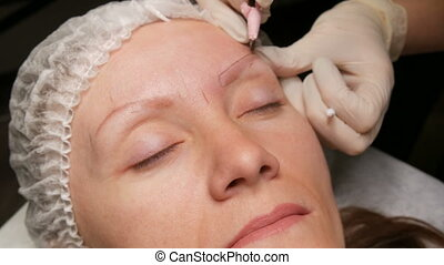 Beautician makes eyebrow correction to his patient. Marking the contour of the eyebrows with a special pencil