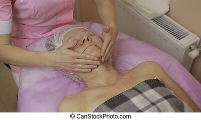 Beautician moisturizing woman's face with cream - Closeup...