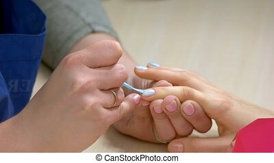 Beautician painting nails close up. Female manicurist...