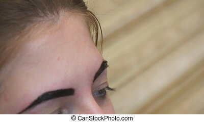 Beautician performs eyebrow correction for a young woman....
