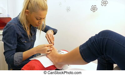 Beautician performs professional pedicure at beauty salon