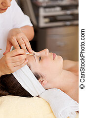 Beautician plucking a woman's eyebrows