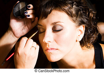 make-up - beautician preparing young bride for the wedding...