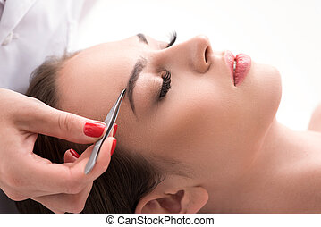 Beautician pulling out female brows - Close up of skillful...