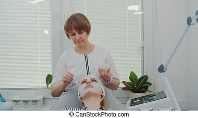 Beautician putting cream mask on woman's face at beauty salon. Facial skin care treatments.