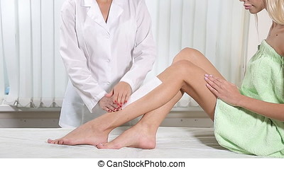 Beautician removing leg hair with wax. - Beautician removing...