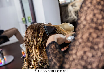 Beautician Styling Client's Hair In Salon