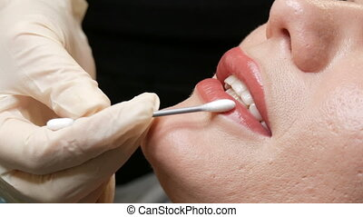 Beautician touches a cotton swab to permanent tattoo lip makeup. Light matte pink lips close up. Lips microblading procedure