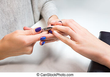Beautician trimming cuticles of female client