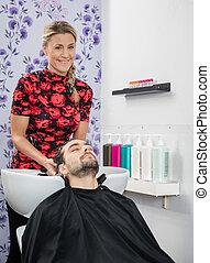 Beautician Washing Male Customer's Hair In Salon