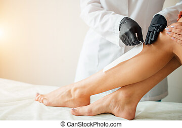 Beautician waxing a woman leg applying a strip of material over the hot wax