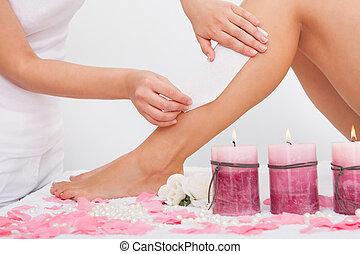 Beautician Waxing A Woman's Leg Applying Wax Strip