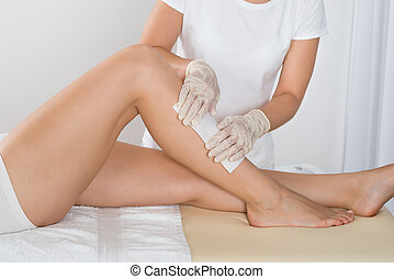 Beautician Waxing Leg Of Woman With Wax Strip At Beauty ...