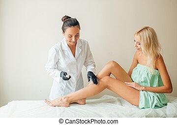 Beautician waxing woman a leg at salon. Depilation.