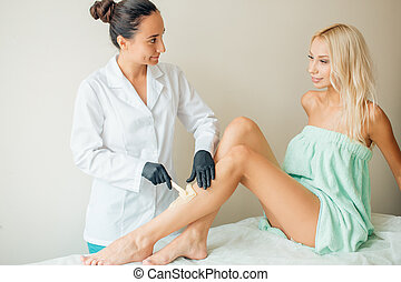 Beautician waxing woman a leg at salon. Depilation.