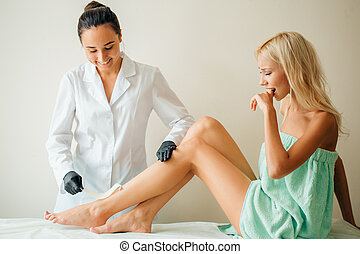 Beautician waxing woman leg with depilation strip at salon