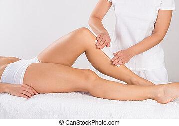 Beautician Waxing Woman's Leg At Salon