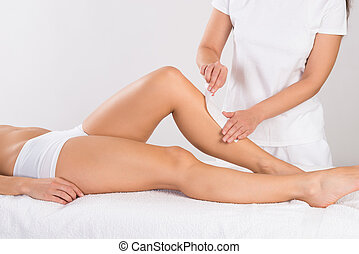 Beautician Waxing Woman's Leg At Salon - Midsection of...