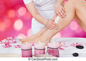 Beautician Waxing Woman's Leg In Beauty Salon - Midsection...