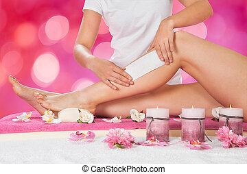 Beautician Waxing Woman's Leg In Salon