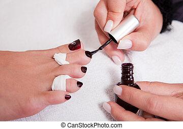 Beautician working on toenails. Spa studio shot