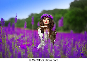 Beautidul brunette teen girl sends an air kiss over wild flowers field nature background. Attractive young woman with wheat on head, long curly hair.