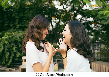 Beauties in style. Two beautiful young well-dressed women smiling at camera while standing embracing outdoors