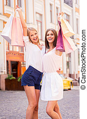 Beauties with shopping bags. Two attractive young women holding shopping bags and smiling while standing outdoors
