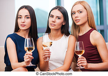 Beauties with wine. Three beautiful young women in evening gown sitting on the couch and holding glasses with wine