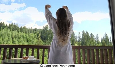 Beautifl young woman waking up at morning and stretching out hands on hotel room while looking on forest and mountains. Concept of tourism and vacation in mountains at summer.