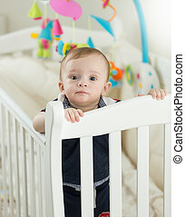 Beautiful 9 months old baby boy standing in crib at bedroom