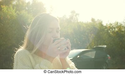 Beautiful admiring woman drinking hot tea from thermos cup