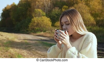 Beautiful admiring woman drinking hot tea from thermos cup -...