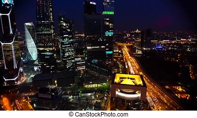 Beautiful aerial drone view on bright evening night Moscow city illumination in busy metropolis downtown cityscape