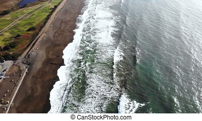 beautiful aerial video of big blue ocean waves approaching the seashore