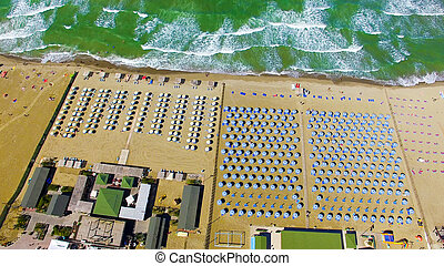 Beautiful aerial view of beach chairs and umbrellas along the ocean