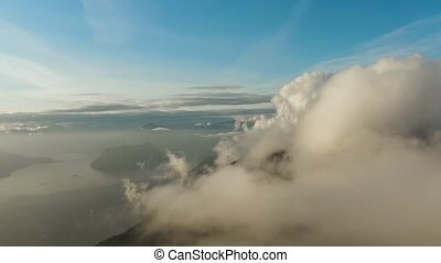 Beautiful Aerial View of Canadian Mountain Landscape during a colorful sunny sunset. White Puffy Clouds. Taken at Howe Sound, West Vancouver, British Columbia, Canada.