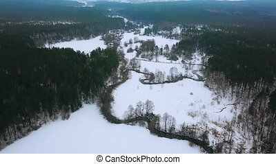Beautiful aerial view of river and forest in winter. Meandring cold river in the middle of forest. Top view on winter forest